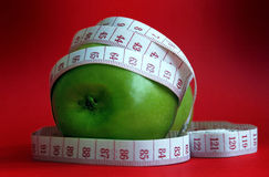 Green apple and tape measure Stock Photos