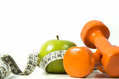 Green apple, tape measure and dumbbells Royalty Free Stock Photos