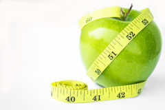 Green Apple with Tape Measure. Green apple fruit with a weight loss aid royalty free stock photos