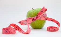 Green apple with tape measure. Green apple with red tape measure Stock Photo