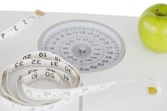 Green apple with a tape measure and a weigh-scale Royalty Free Stock Image