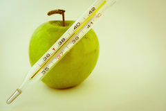 Green apple with thermometer, vintage effect Royalty Free Stock Photography