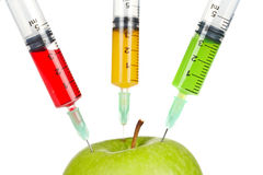 Green apple with three syringes inserted Royalty Free Stock Photos