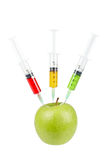 Green apple with three syringes inserted Stock Images