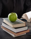 Green apple on top of books Royalty Free Stock Photography