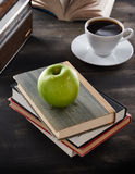 Green apple on top of books Stock Photos
