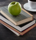 Green apple on top of books Stock Image