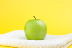 Green apple and towel. Green apple with towel on yellow background Stock Photography