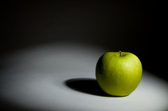 Green apple under the spot. A green apple on stage under the spot Stock Images