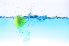 Green apple under water splashing Royalty Free Stock Images