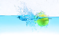 Green apple under water splashing Royalty Free Stock Image