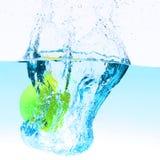 Green apple under water splashing Stock Image