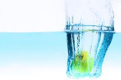 Green apple under water splashing Royalty Free Stock Image