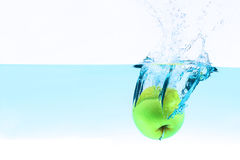 Green apple under water splashing Stock Photo