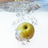 Green apple under water with a trail of transparent bubbles Royalty Free Stock Photos