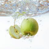 Green apple under water with a trail of transparent bubbles Royalty Free Stock Image