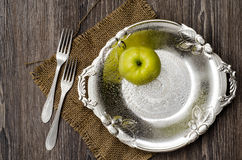 Green apple on vintage plate with two folks Stock Photo