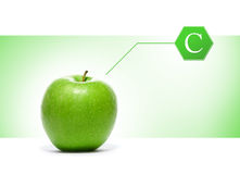 A green apple with a vitamin sign on a light background Stock Images