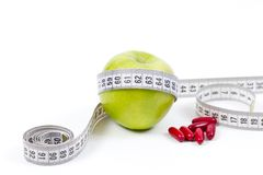 Green apple and vitamins for healthy diet. Green apple and vitamins for a healthy diet with measurement tape Royalty Free Stock Photography