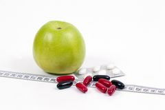 Green apple and vitamins,healty diet. Dieting concept,green apple and vitamins for a healty diet with measurement tape Stock Photography