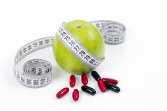 Green apple and vitamins,healty diet. Dieting concept,green apple and vitamins for a healty diet with measurement tape Royalty Free Stock Photo