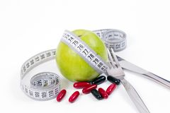 Green apple and vitamins,healty diet. Dieting concept,green apple and vitamins for a healty diet with measurement tape,knife and fork Royalty Free Stock Photos