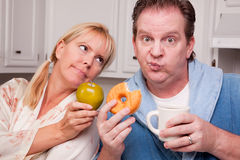 Green Apple vs. Donut Healthy Eating Decision. Couple in Kitchen Eating Donut and Coffee or Healthy Fruit Royalty Free Stock Photos