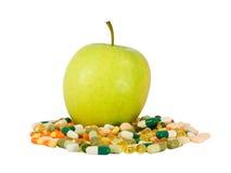 Green apple vs. pills Stock Images