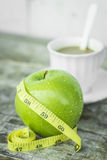 Green apple with waist and measuring tape. And Drinking coffee make fat stock photos