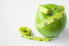 Green apple with waist and measuring tape. Enzyme in apples helps weight loss. In addition to vitamins and minerals that are beneficial to the body. In apples royalty free stock photos