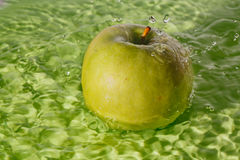 Green apple washing with water splash. Green apple water splashes during cleaning on green plate Royalty Free Stock Photography