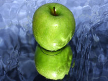 Green apple on water Royalty Free Stock Image