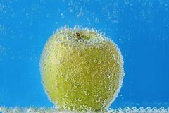 Green apple in water with bubbles on blue background royalty free stock image