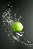 Green apple with water splash, on black Stock Images