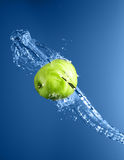 Green apple with water splash, on blue water Royalty Free Stock Images