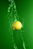 Green apple with water splash, on green stock photography