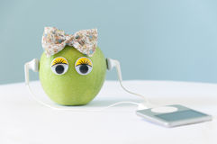 Green apple wearing headphones Stock Images