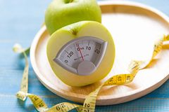 Green apple with weight scale and measuring tape for the healthy diet slimming . Diet and Healthy Concept Royalty Free Stock Photos