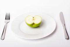 Green apple on white plate Royalty Free Stock Photos