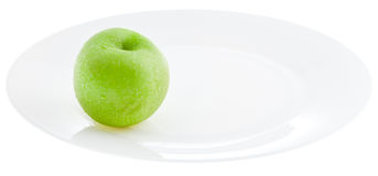 Green apple on white plate Royalty Free Stock Images