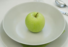 Green apple on white plate Stock Images