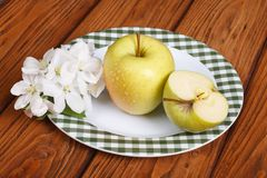 Green apple on a white plate and flowers Royalty Free Stock Photo