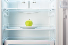Green apple on white plate in open empty refrigerator Stock Photos