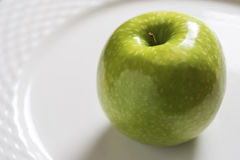 Green Apple on the White Plate. Shiny Organic Granny Smith Close Up. Green Apple on the White Plate. Organic Granny Smith Close Up Royalty Free Stock Images