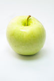 Green apple on white surface Stock Photography