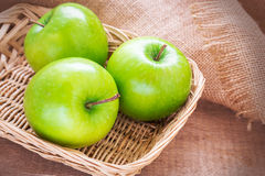 Green apple in wicker basket Stock Image