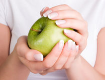 Green apple in woman's hands Stock Images