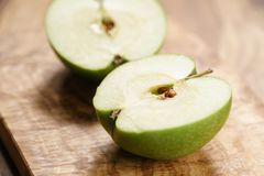 Green apple on wood board closeup. Shallow focus Stock Images