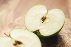 Green apple on wood board closeup. Shallow focus Royalty Free Stock Photography
