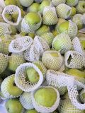 Green apple wrapped in foam, put up for sale fruit market. Closed up Green apple wrapped in foam, put up for sale fruit market royalty free stock photo